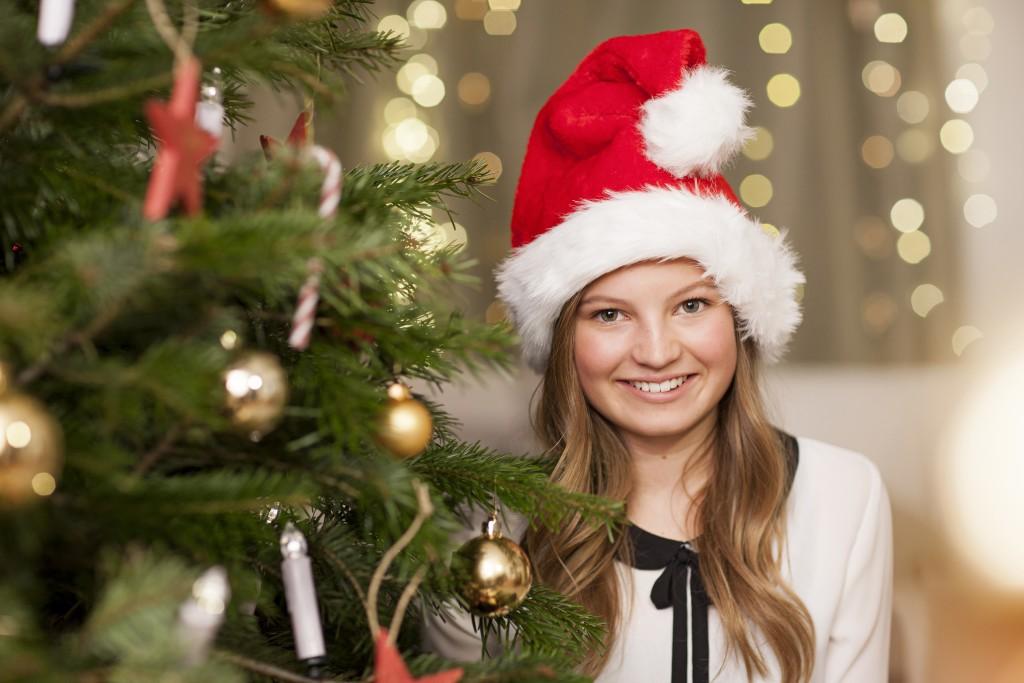 Božični portret ob okrašenem drevesu z zamegljenim ozadjem