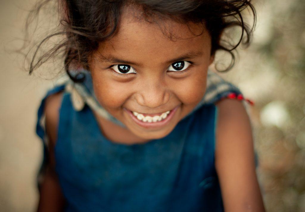 nasmejana deklica s črnimi lasmi, temno rjavimi očmi in v modri majici