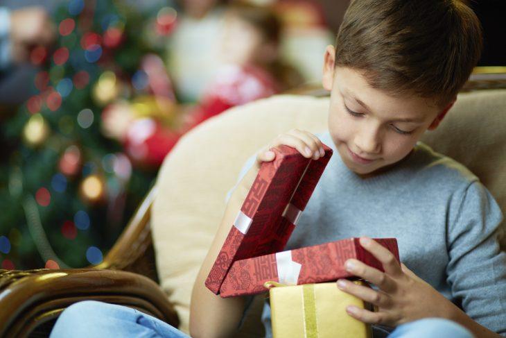 fantek na kavču, ki odpira rdečo darilno škatlo