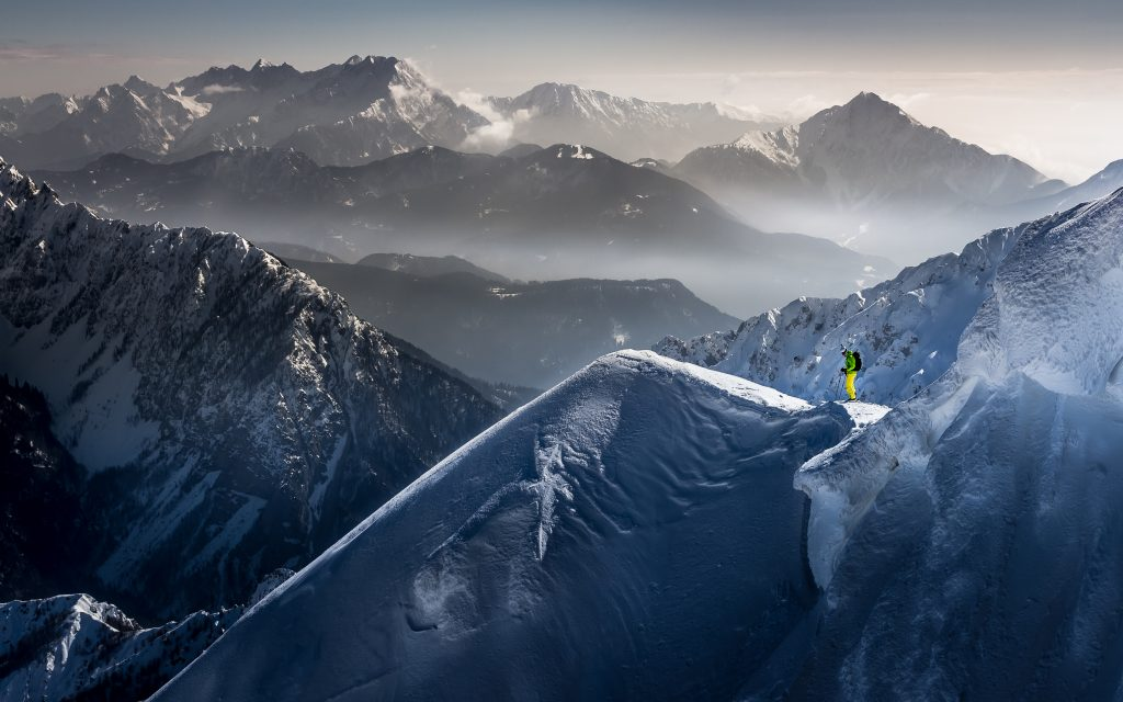 smučar v zeleno-rumeni obleki, sredi gora pokritih s snegom