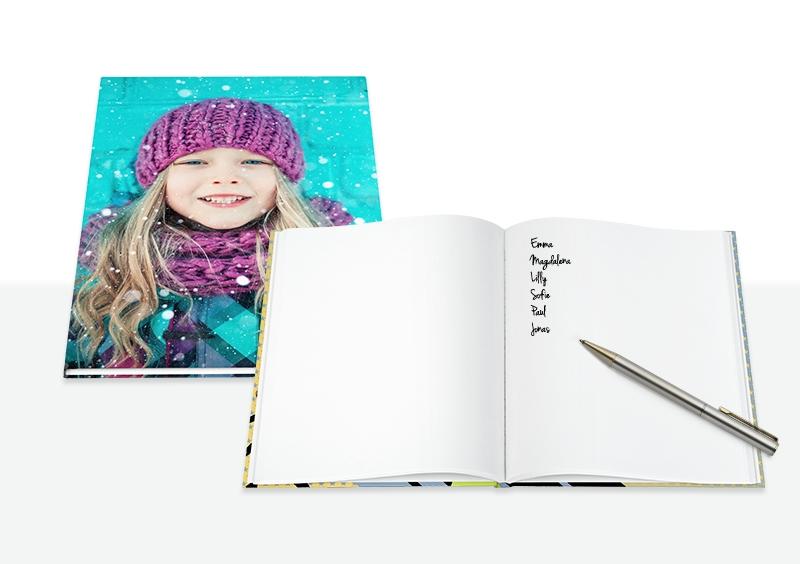 zvezek s portretom deklice in odprt brezčrtni zvezek s svinčnikom
