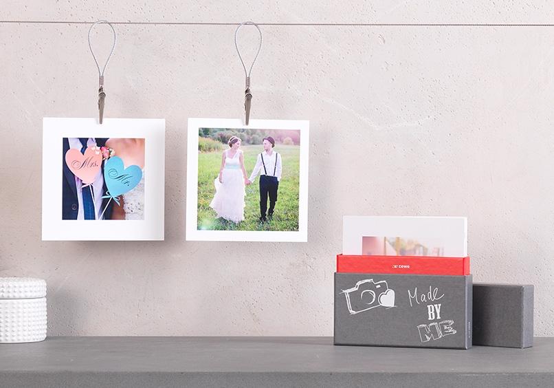 obešene kvadratne fotografije s ščipalkami in darilno škatlo