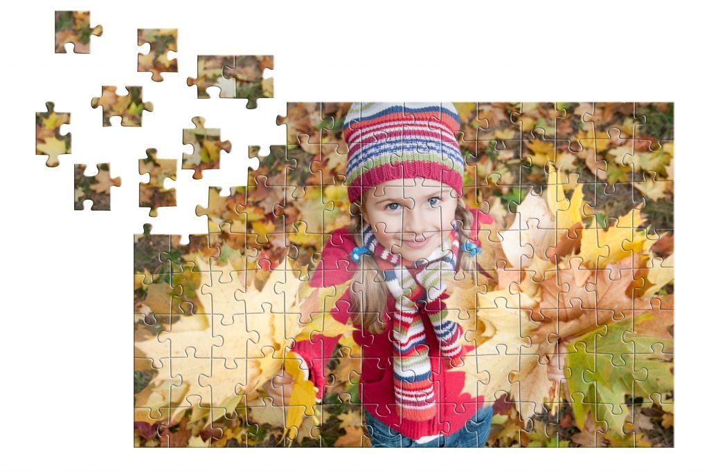 Puzzle z motivom deklice s pisanim šalom in kapo, obdana z rumenim listjem