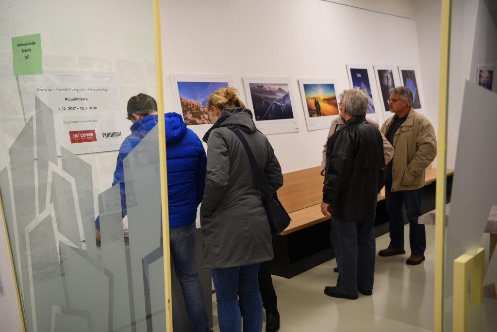 Obiskovalci fotografske razstave in obešene fotografije v Slovenskem planinskem muzeju