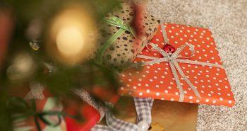 darilo v rdečem darilnem papirju s pentljo pod božičnim drevescem