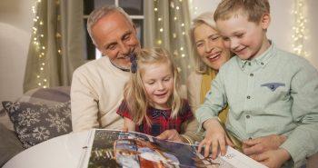 stari starši z vnukinjo in vnukom v naročju gledajo koledar s fotografijami