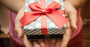 škatla v darilnem papirju z rdečo pentljo
